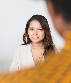 creating a resume leads to an interview. A woman being interviewed.